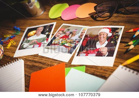 High angle view of office supplies and blank instant photos against smiling man opening a gift on christmas day