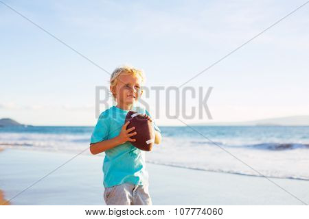Young Boy Playing Catch Throwing Football on the Beach