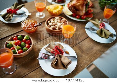 Glasses with juice, vegetables, nuts and plates with napkins and silverware