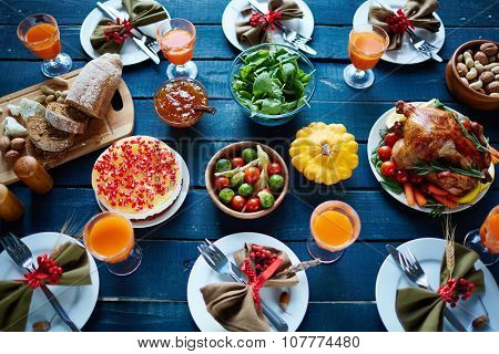 Roasted turkey, glasses with juice, vegetables, nuts, dessert, fresh bread and tableware on dinner table
