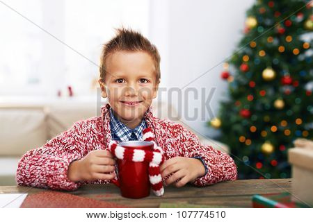 Cute youngster with red cup looking at camera
