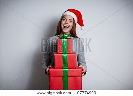 Ecstatic girl in Santa cap holding heap of gift-boxes