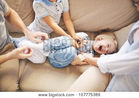 Happy girl laughing while her mother and brother tickling her