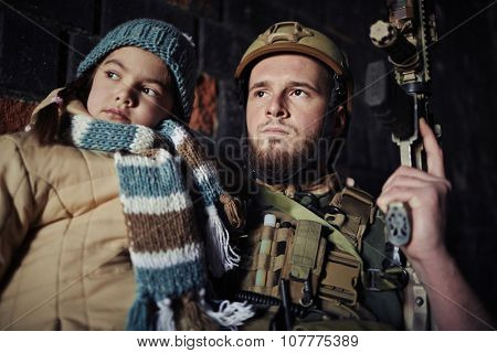 Military man in camouflage holding gun and little girl
