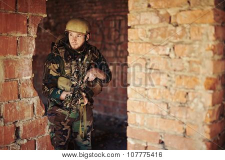 Young soldier in military camouflage standing by brick wall with gun