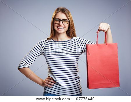 Modern shopper in casualwear and eyeglasses looking at camera