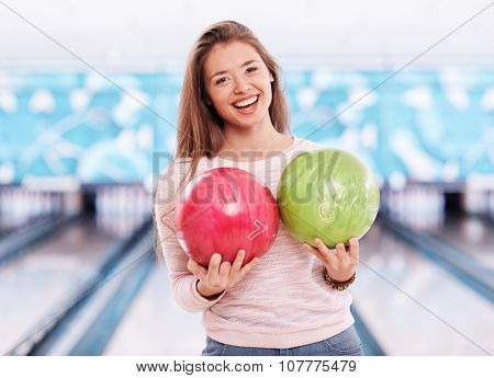 Happy girl with in casualwear holding two bowling balls