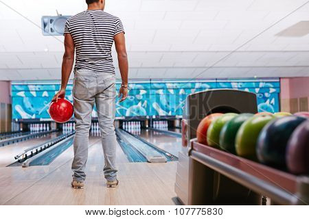 Young guy in casualwear playing bowling