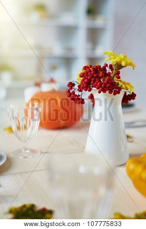 Autumn ashberries, flowers, and glassware on festive table