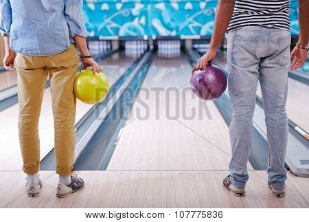 Young people in casualwear standing in bowling alley