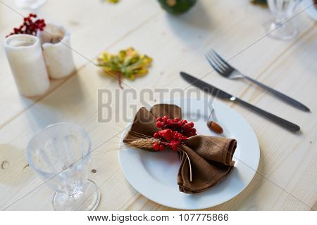 Ripe ashberries, napkin, acorn on plate with glass, fork and knife near by