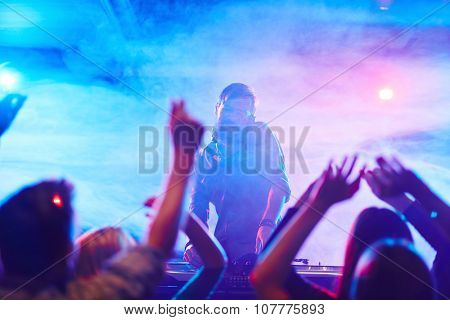 Energetic deejay and dancing crowd enjoying disco in night club
