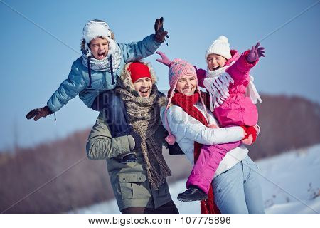 Ecstatic family in winterwear looking at camera outdoors