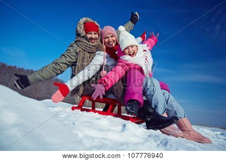 Father, mother and daughter on sledge having fun in winter