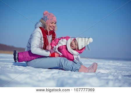 Happy female in winterwear playing with her daughter in snowdrift