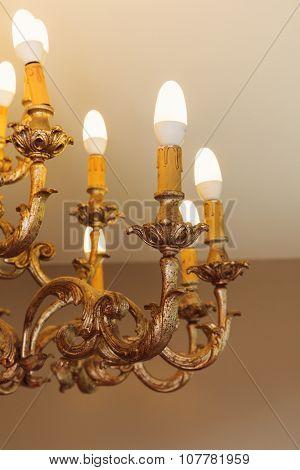 Detail of chandelier alight, golden