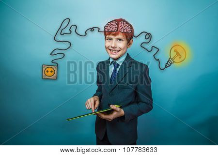 Teenage boy in suit smiling and working in the tablet charging c