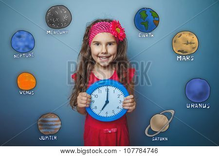Teen girl laughs holding her hands round the clock blue planet o