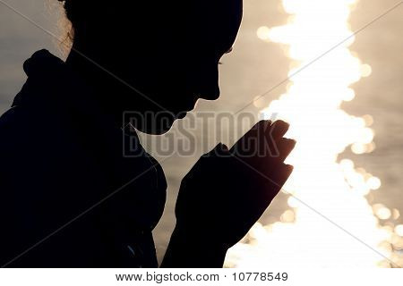 Silhouette woman profile face prays folding arms near sunset water