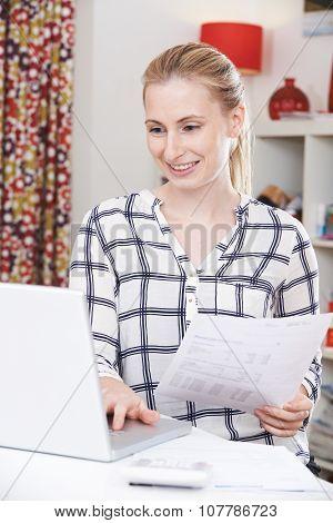 Young Woman Looking At Domestic Bills
