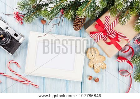 Christmas photo frame on wooden table with tree, camera and gift box. Top view with copy space