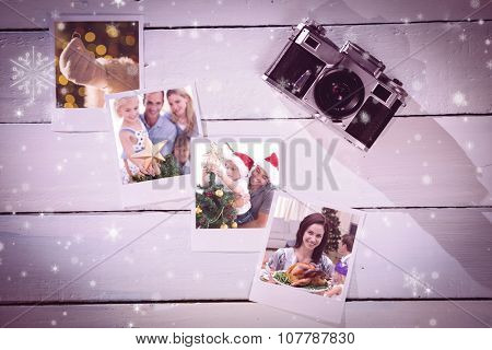 Happy father helping his son to put an angel on the Christmas tree against instant photos on wooden floor