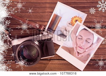 Attractive woman receiving facial massage at spa center against lighted candles with an orange gerbera on towels