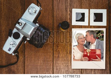 Senior man giving a kiss and a Christmas present to his wife against view of an old camera with photos slides
