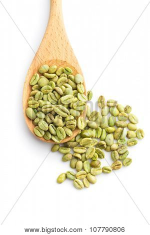 green coffee beans in wooden spoon on white background