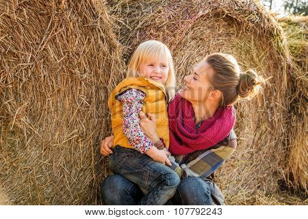 Portrait Of Woman And Happy Child Sitting On Hay On Farm