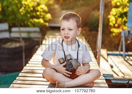 Little Boy Looking Through Camouflage Binoculars On River Bank