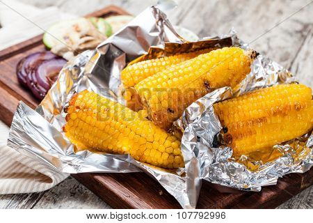 Grilled corn cobs on wooden plate
