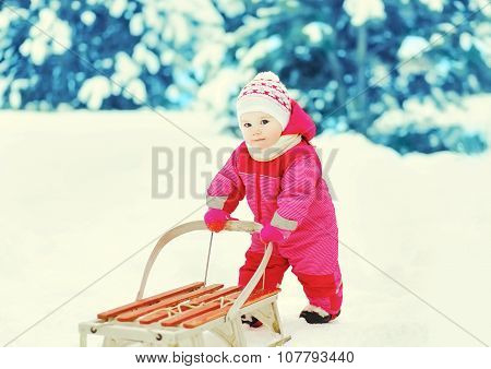 Cute Little Child Playing With Sled In Winter Forest
