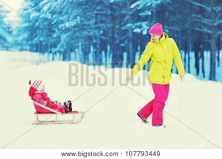 Happy Mother And Child Walking In Winter Forest. Mom With Baby On Sled