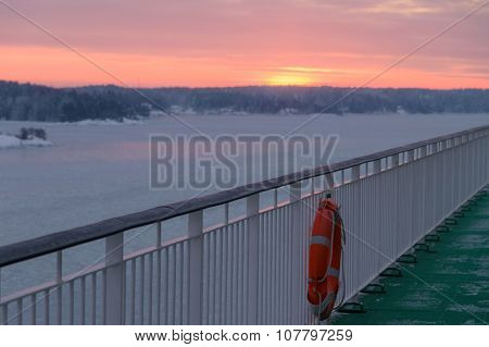 Deck Of Ferry With Life-buoy, Winter Sunrise On Background