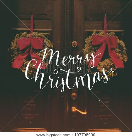 Merry Christmas - calligraphy text overlay on filtered photo with decor wreaths on the vintage door.