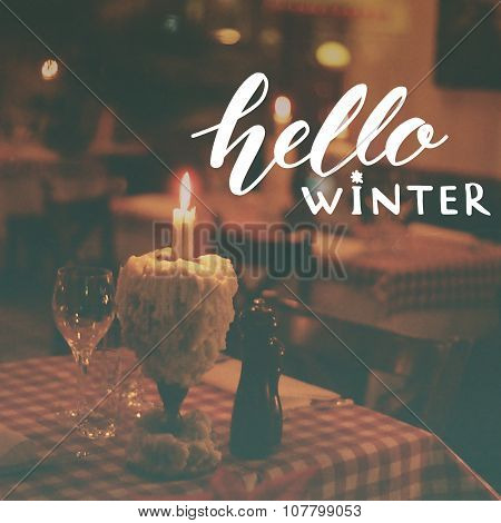 Hello winter text overlay on toned photo of restaurant table with candle and wine glass. December gr