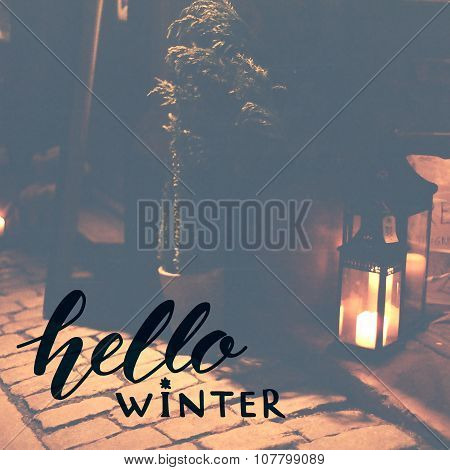Hello winter. Inspirational phrase handwritten on toned photo of lantern with candle. December greet