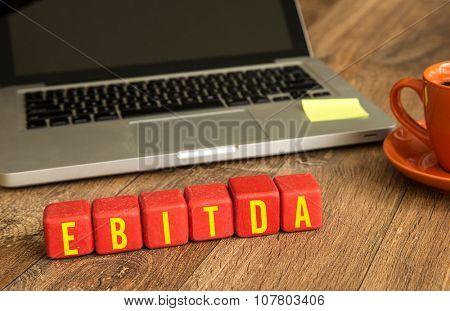 Ebitda written on a wooden cube in office desk