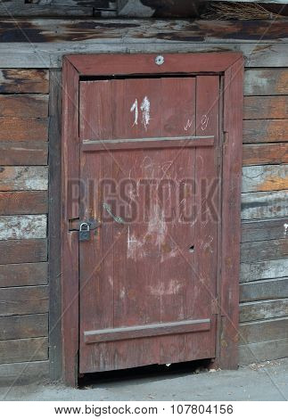 old wooden doors and compound wall of a shed made of planks and bricks