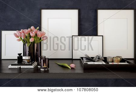 Blank picture frames on black table with candles and tulips in a vase.