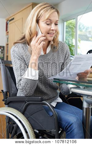 Woman In Wheelchair Making Phone Call Whilst Reading Letter