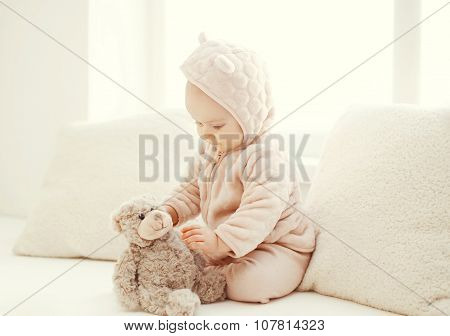 Cute Baby Playing With Teddy Bear Toy At Home In White Room