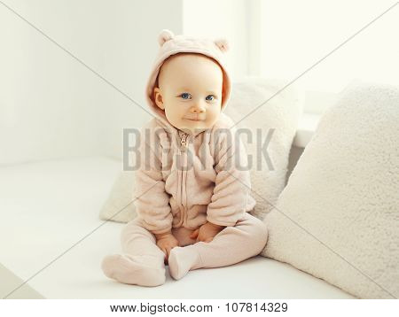 Cute Smiling Baby Sitting In White Room At Home