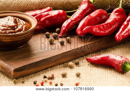 Red Sauce, Spices And Pepper On A Kitchen Board