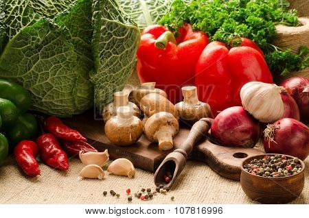 Vegetables, Mushrooms And Spices On A Kitchen Board On Sacking