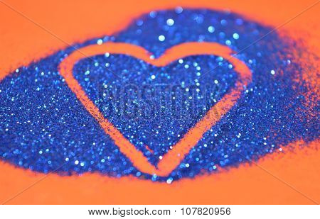 Blurry abstract background with heart of blue glitter sparkle on red surface