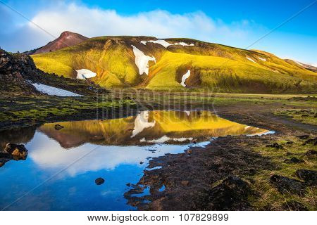 The  sunrise in Iceland. Light golden dawn illuminates the mountains and glaciers national park Landmannalaugar