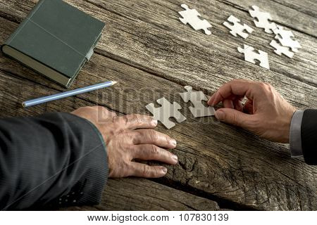 Teamwork And Cooperation Between Two Business People As They Join Forces To Combine Matching Puzzle