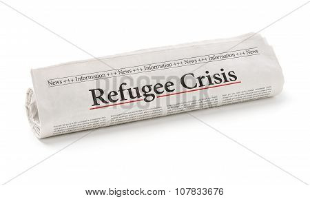Rolled Newspaper With The Headline Refugee Crisis